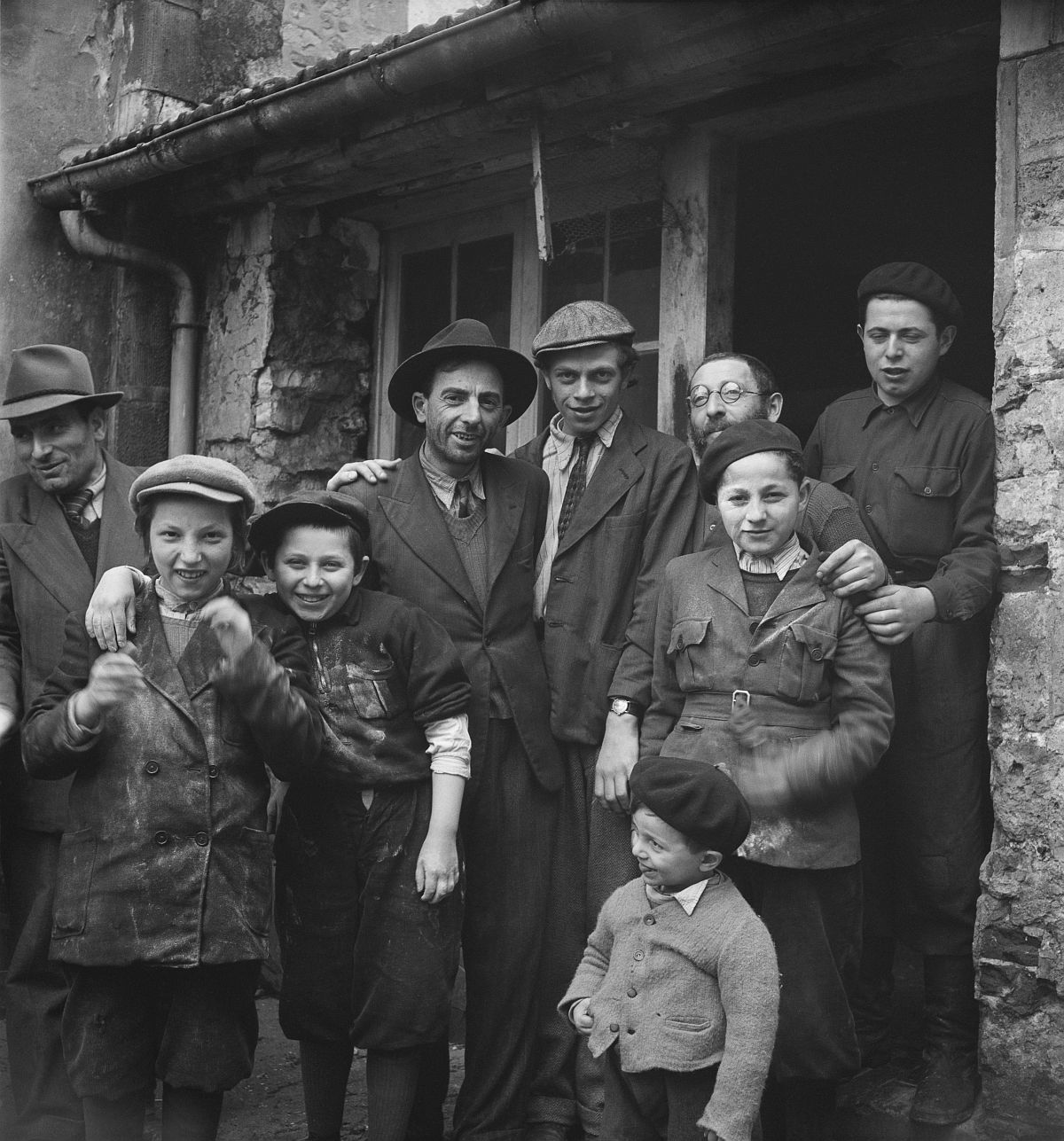Roman Vishniac, [Holocaust survivors gathering outside a building where matzoh is being made in preparations for the Passover holiday, Hénonville Displaced Persons' Camp, Picardy, France], 1947. Ink-jet print. © Mara Vishniac Kohn, courtesy International Center of Photography.