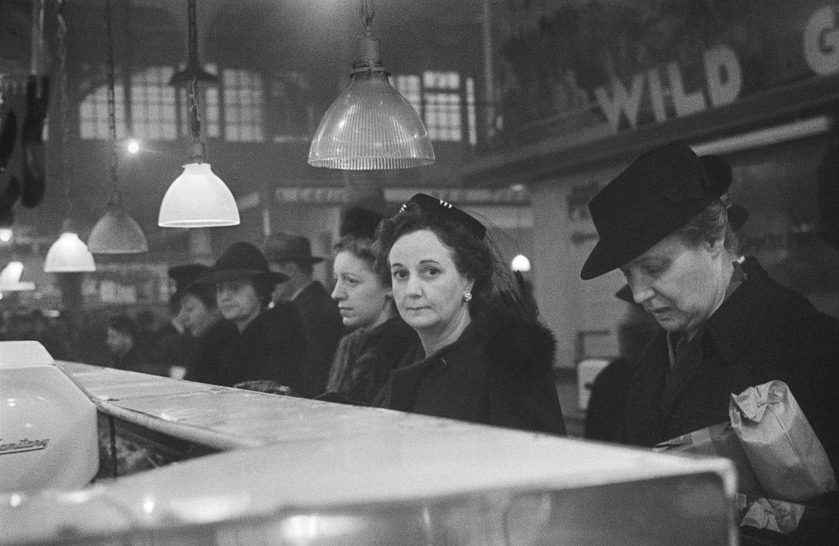 Roman Vishniac, [Customers waiting in line at a butcher's counter during wartime rationing, Washington Market, New York], 1941–44. Ink-jet print. © Mara Vishniac Kohn, courtesy International Center of Photography.