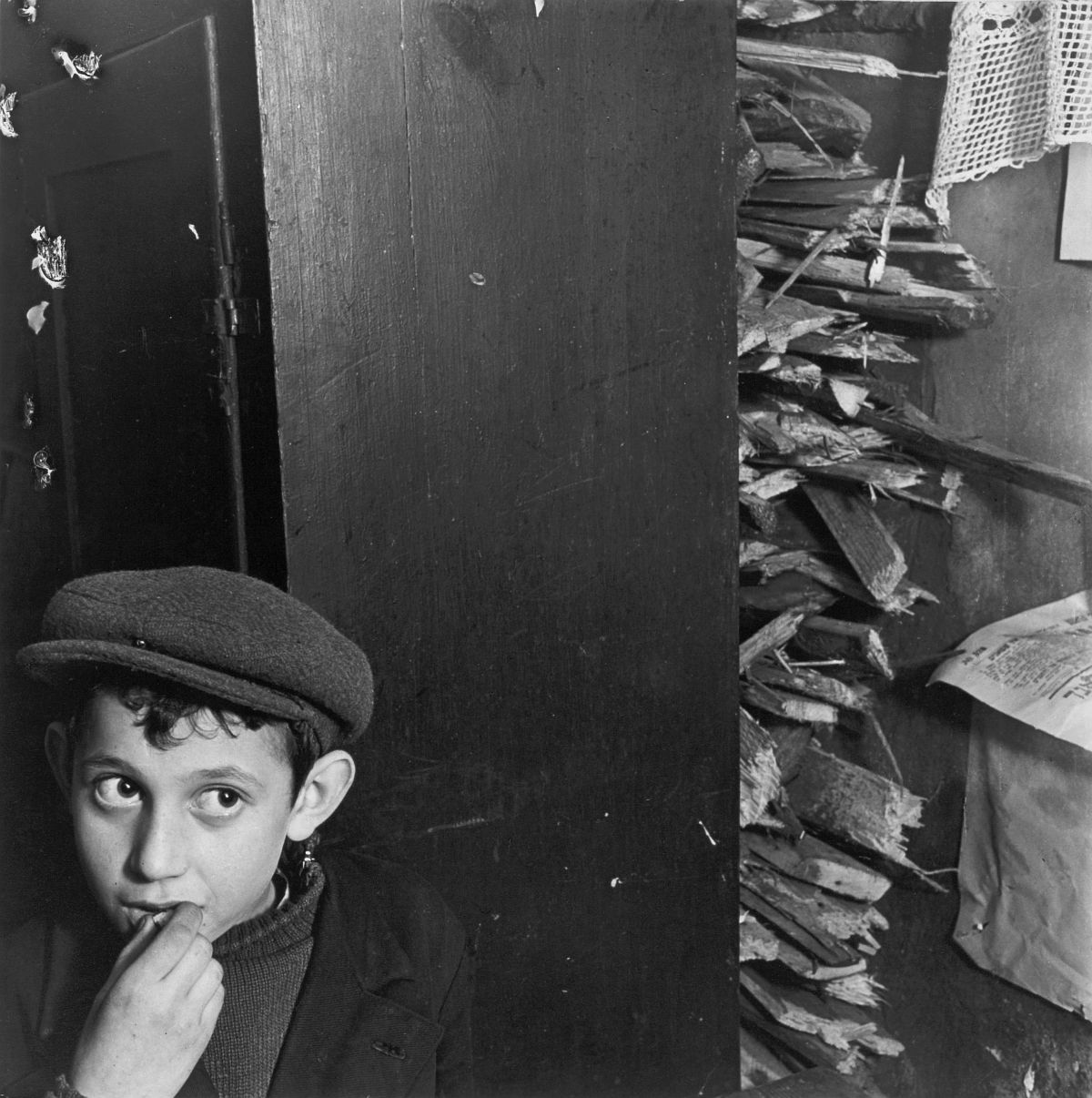 Roman Vishniac, [Boy with kindling in a basement dwelling, Krochmalna Street, Warsaw], ca. 1935–38. Gelatin silver print. © Mara Vishniac Kohn, courtesy International Center of Photography.