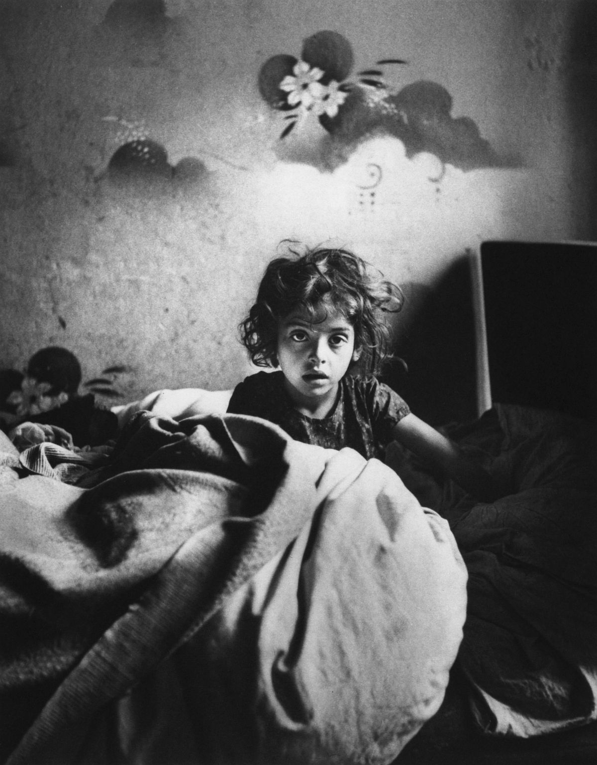 Roman Vishniac, [Sara, sitting in bed in a basement dwelling, with stenciled flowers above her head, Warsaw], cs. 1935–37. Platinum print. © Mara Vishniac Kohn, courtesy International Center of Photography.
