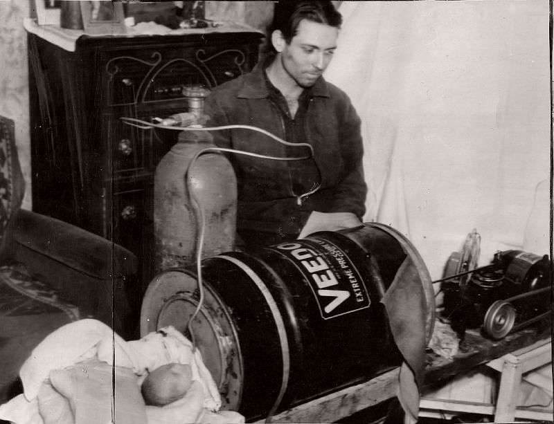 "In this photo dated March 15, 1940, the caption stated ""Homemade Iron Lung failed to save life despite ingenuity of father. James Bailey, 25 watching operation of device on his baby son, Paul which kept him alive two days. The infant died soon after. Bailey fashioned the apparatus from an oil barrel, washing machine parts, and rubber tire tubing."""