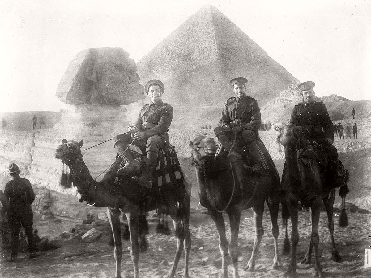 Three unidentified New Zealand servicemen riding camels during World War I, the Sphinx and a pyramid in the background. # James McAllister / National Library of New Zealand