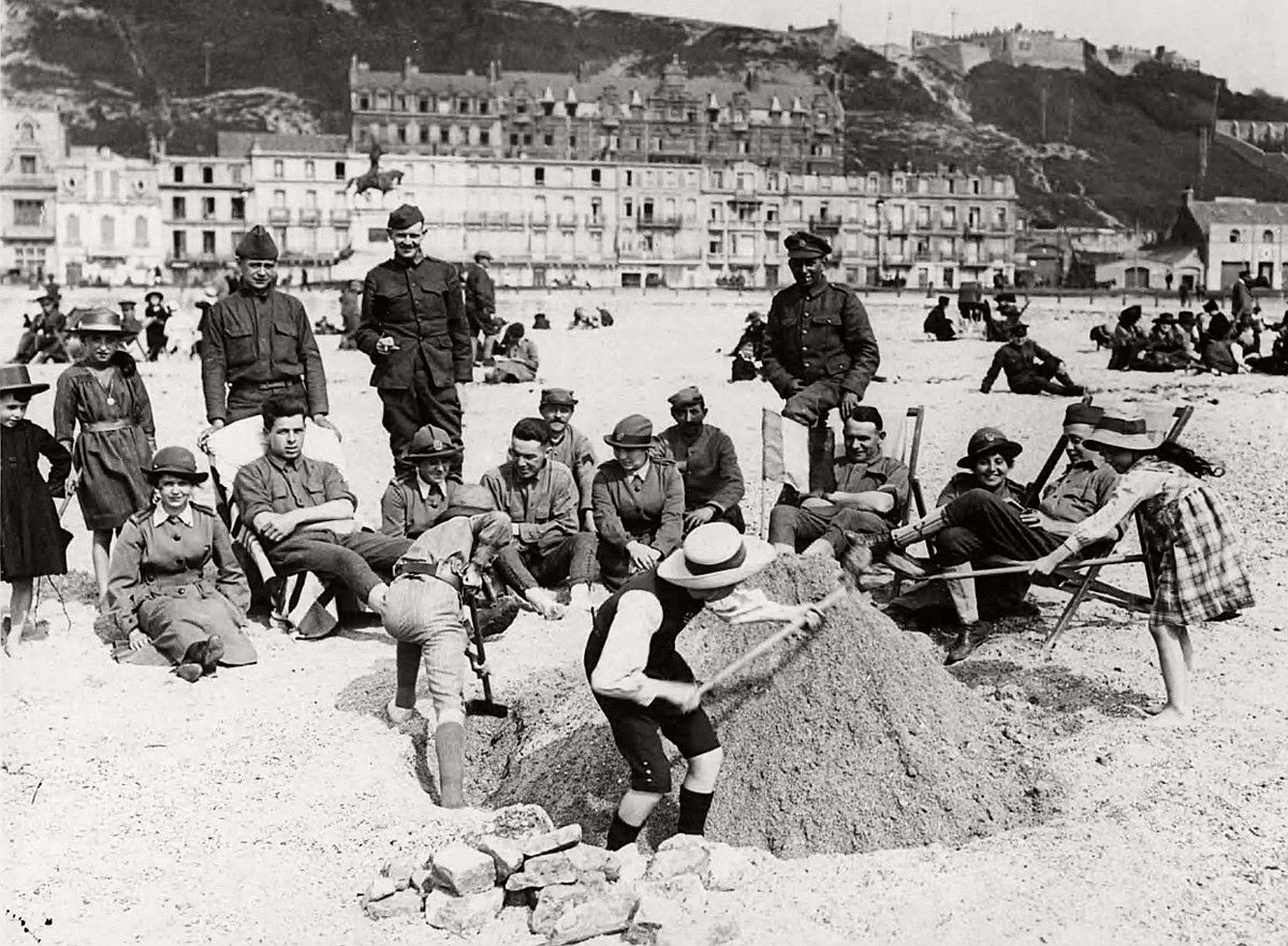 During downtime, soldiers from Britain, France and the USA, plus some members of the Women's Auxiliary Army Corps (WAAC) watch French children playing in the sand, in France, during World War I. # National Library of Scotland