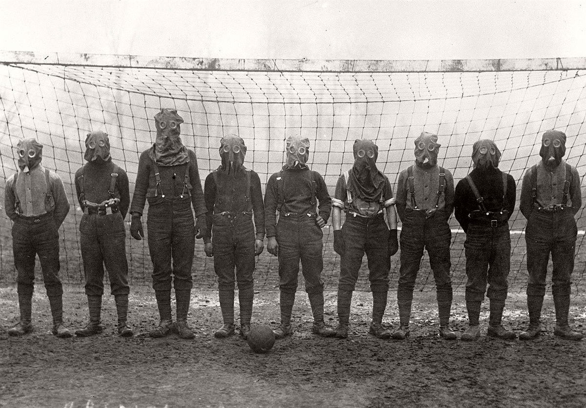 British soldiers play football while wearing gas masks, France, 1916. # Bibliotheque nationale de France