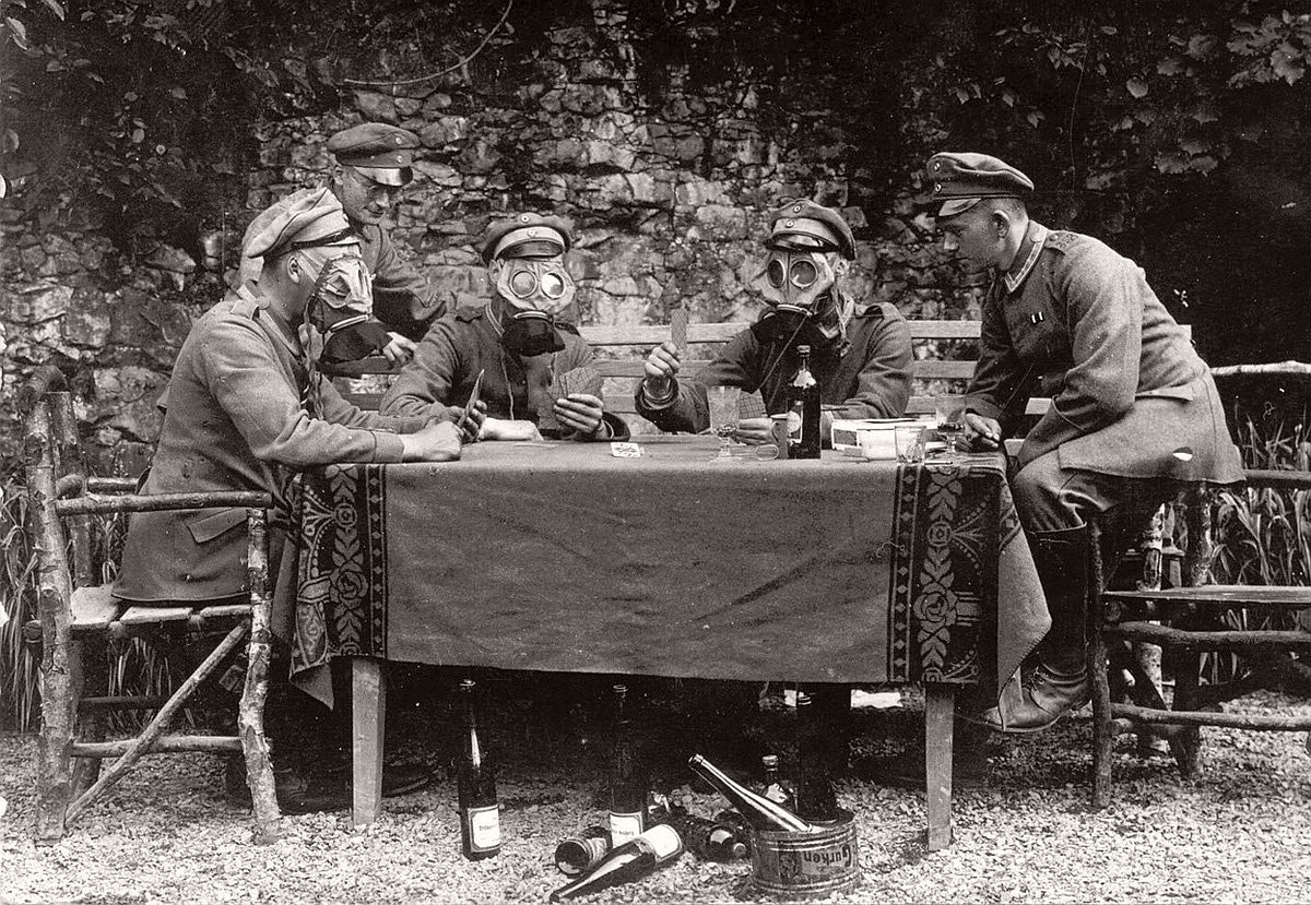German NCOs from Infanterie-Regiment No. 358 pose for the photographer as if they were drinking wine, feasting on gherkins and playing cards while wearing gas masks. # Brett Butterworth