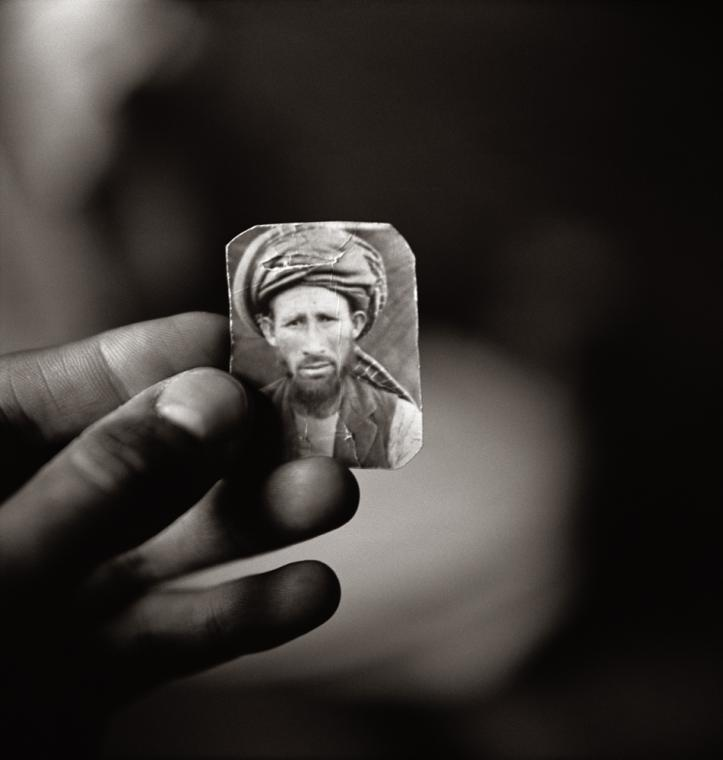 Fazal Sheikh, Abdul Aziz holding a photograph of his brother Mula Abdul Hakim, Afghan refugee village Khairabad, North Pakistan, 1997, from the series The Victor Weeps. © Fazal Sheikh