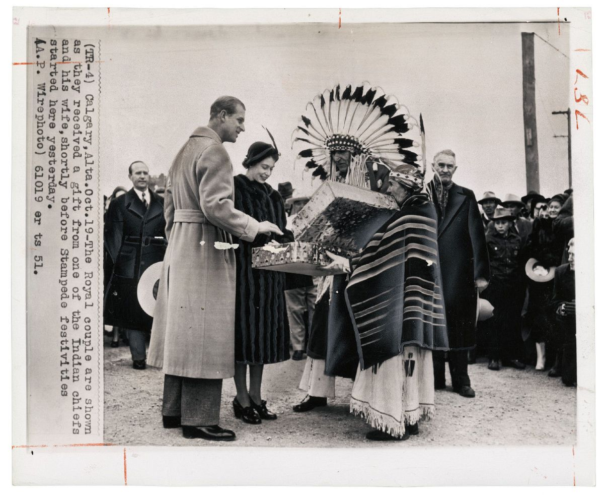 Unknown photographer for The Associated Press, Untitled [Princess Elizabeth and the Duke of Edinburgh receiving a gift from Chief Little Dog (Kainai Nation) and his wife Antoinette Heavy Shield (Siksika Nation) before the Stampede, Calgary, Alberta], October 19, 1951. Photo courtesy of the Rudolph P. Bratty Family Collection, Ryerson Image Centre.