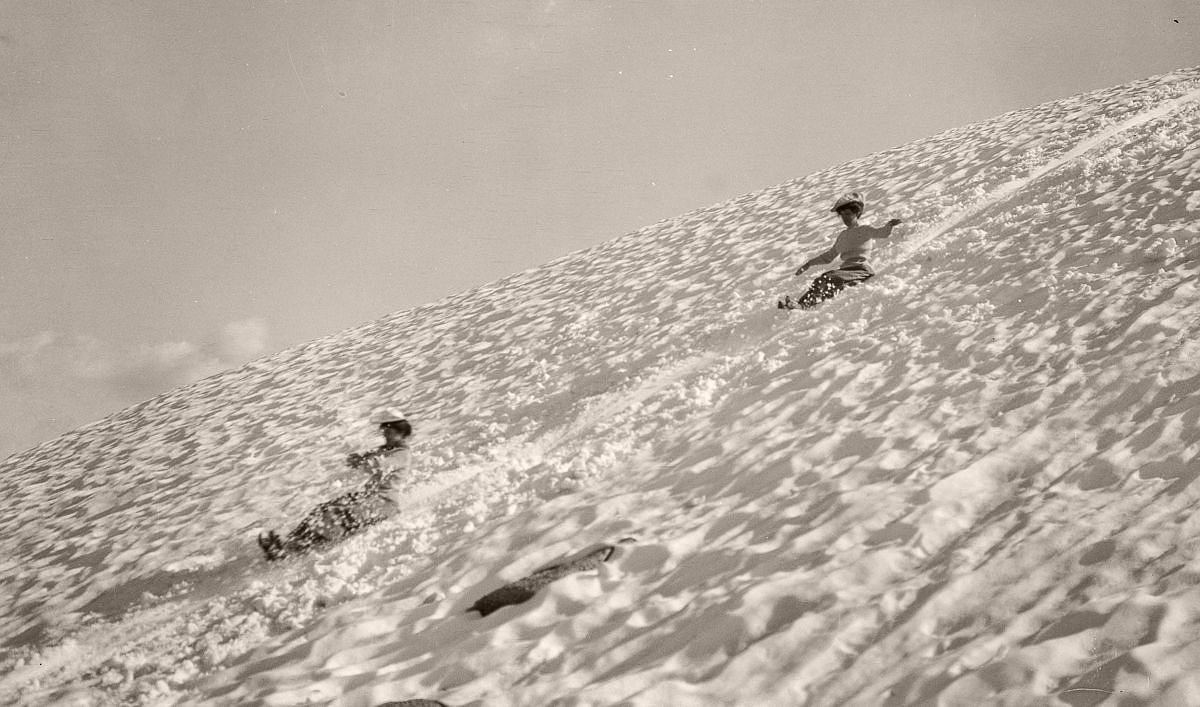 Tourists slide down a slope in Yosemite, 1903. (Library of Congress)