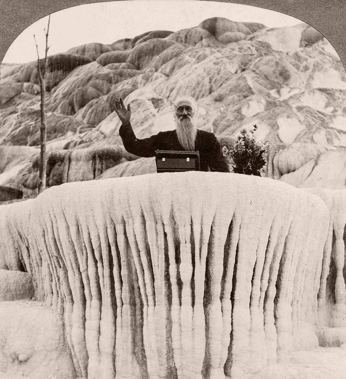 "A man stands behind the ""Pulpit Terrace"" formation at the Mammoth Hot Springs in Yellowstone, 1904. (Library of Congress)"