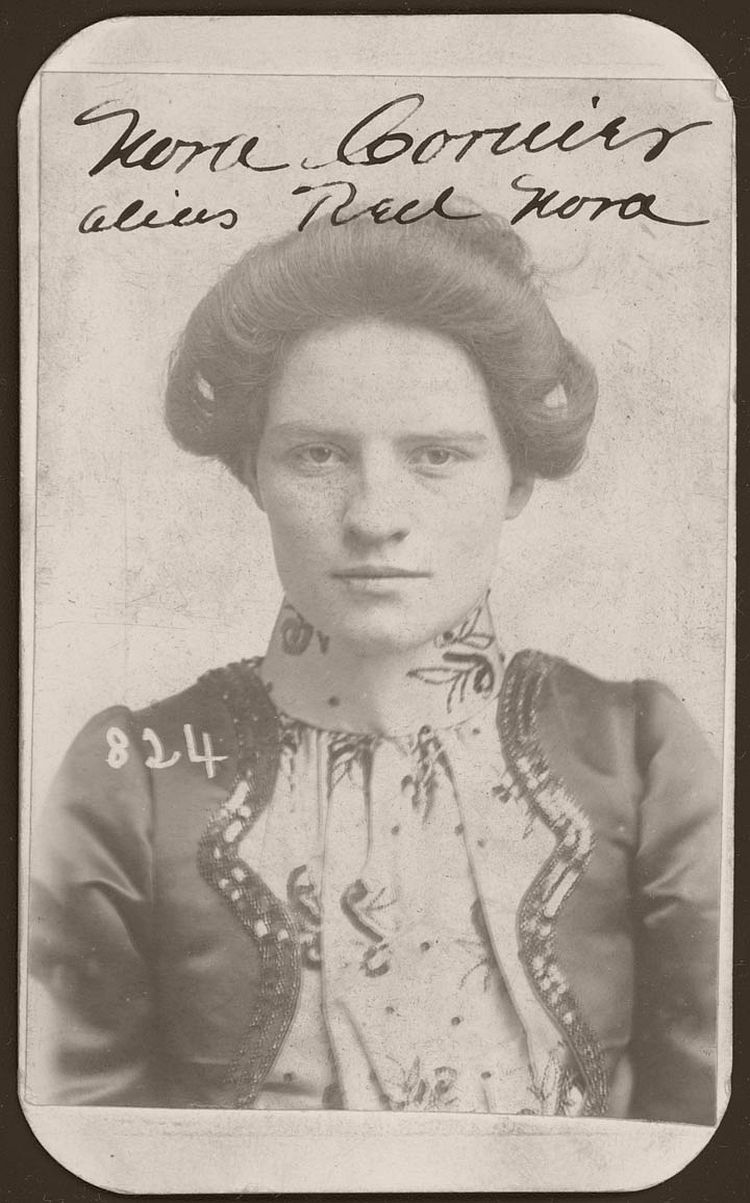 "Meet Nora Courier, better known as ""Red Nora."" On March 31, 1901, Omaha police arrested Nora for stealing a horse. According to police court records, she was 22 years old and stood 5 feet, 3 inches tall. She had slate blue eyes and a scar on the center of her forehead."