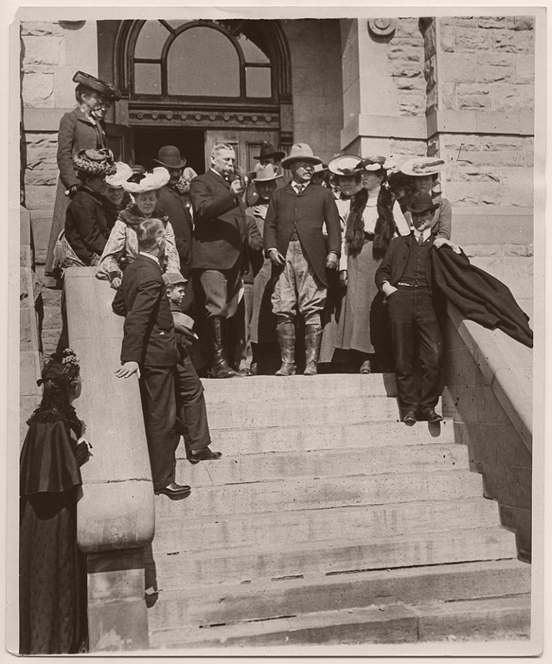 President Theodore Roosevelt receiving a pair of spurs from Francis Warren, United States Senator for Wyoming at the Cheyenne Public Building, which served as courthouse for the District of Wyoming. Presidential Secretary, William Loeb, Jr., is seen immediately behind Senator Warren. President Roosevelt was also given a horse and saddle while in Cheyenne. June 1, 1903.