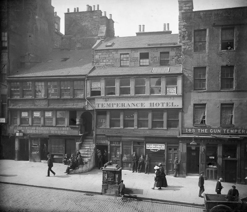 High Street between Canongate and North Bridge, Edinburgh showing no 153 Allan Ramsay's House, The Temperance Hotel, no 143 The Gun'Temperance and The Gun Coffee House, c. 1900.