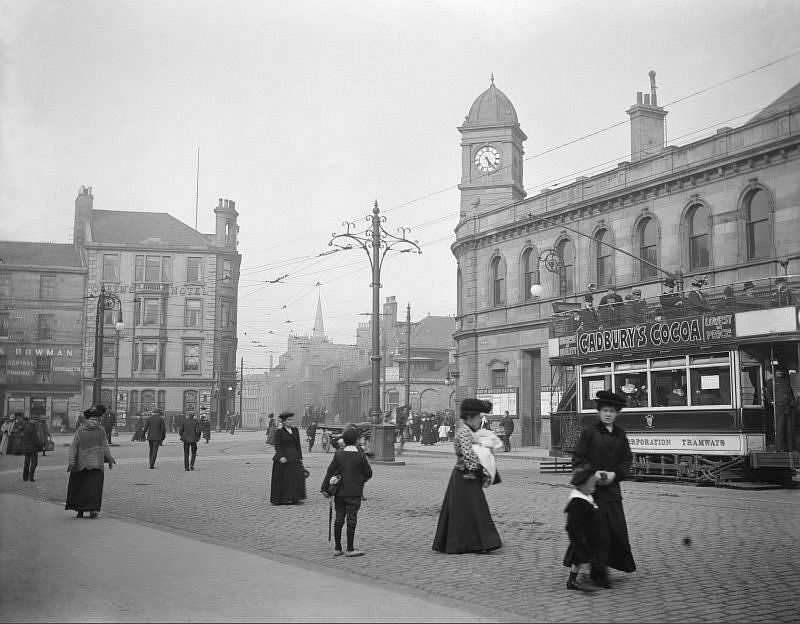 View of Leith Central Station, Edinburgh, from Leith Walk, with street scene and tram advertising Cadbury's Cocoa, 1912. The station opened in 1903 and closed for regular passenger traffic in 1952. Visible is also the Queen's Hotel.
