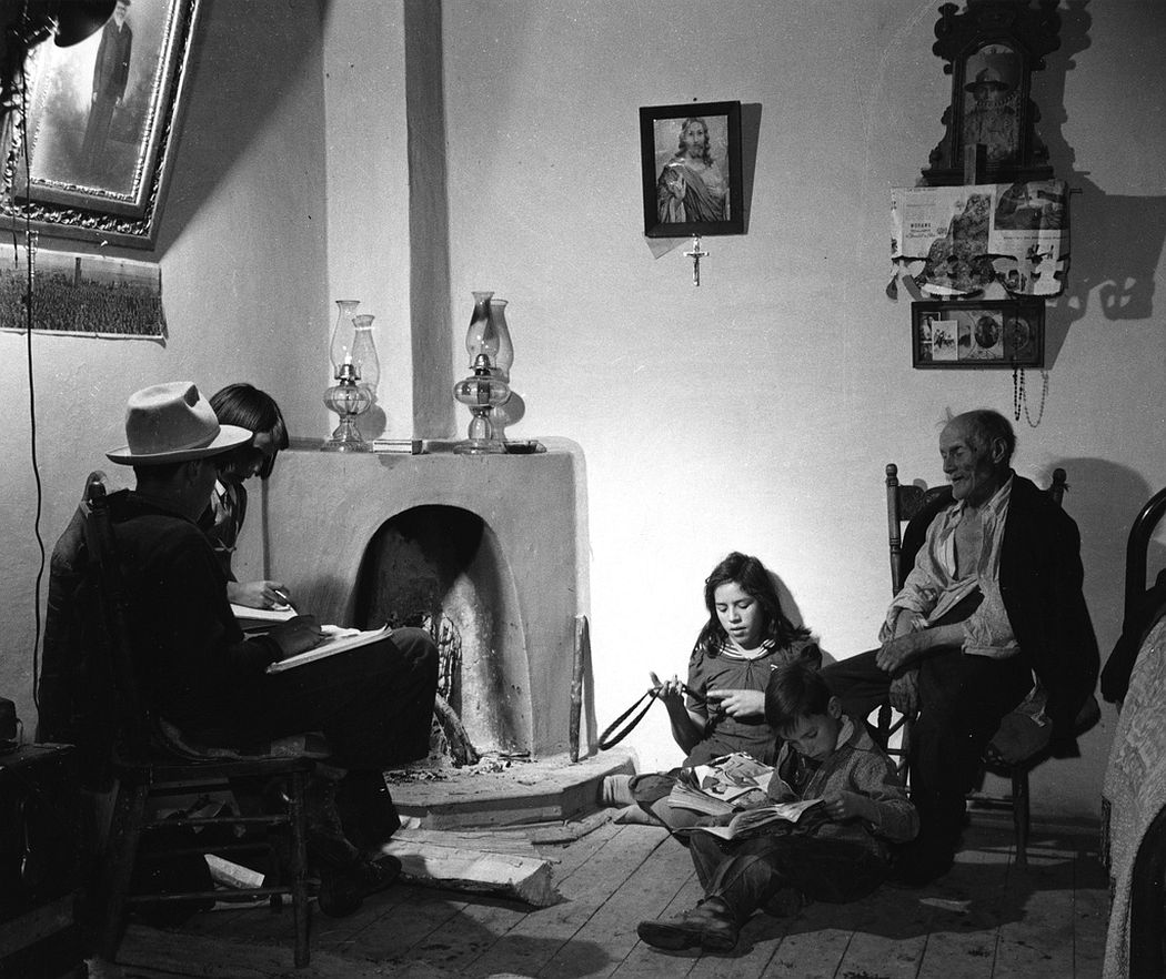 A family in front of kiva fireplace, Trampas, New Mexico, 1943