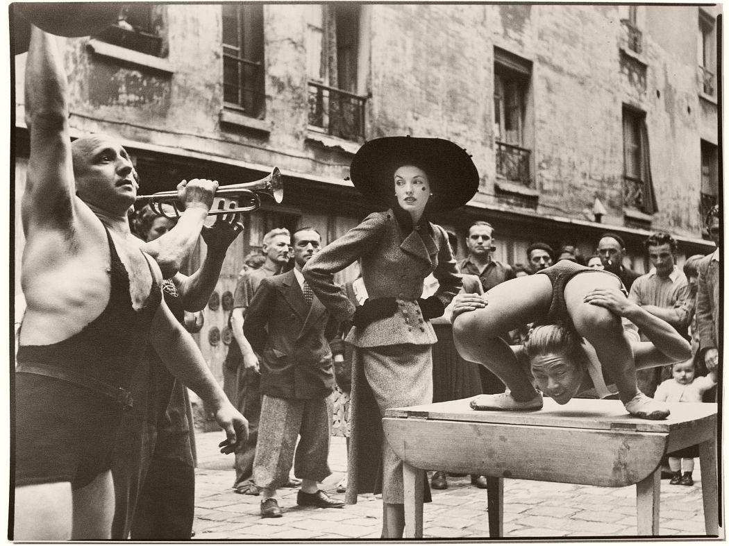 Elise Daniels with street performers, Suit by Balenciaga, Le Marais, Paris, August, 1948 by Richard Avedon