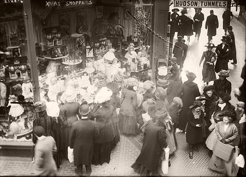 Shoppers gather around a window, 1900.