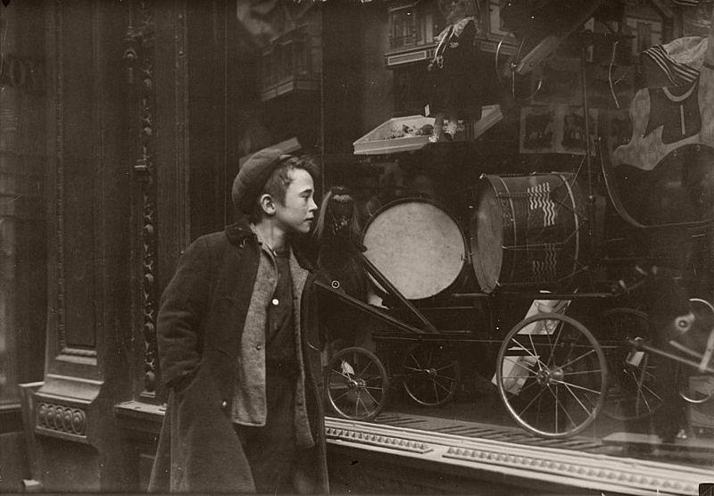 Boy looking at Xmas toys in shop window, 1900.