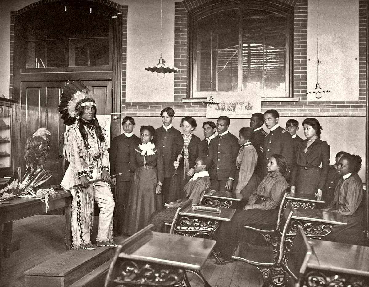 Louis Firetail (Sioux, Crow Creek), wearing tribal clothing, giving a presentation in an American history class, Hampton Institute, Hampton, Virginia, 1899-1900