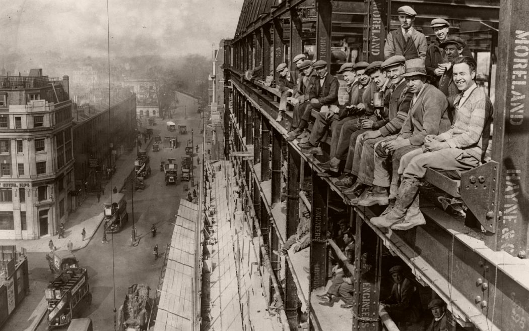 Construction workers taking lunch break on the edges of the building they're working on, London, 1929.