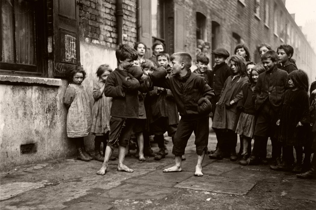 Boys boxing barefoot while their friends look on, London, 1920.