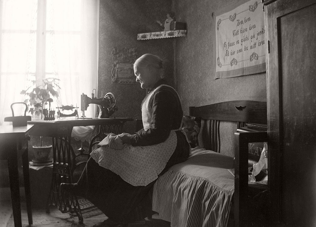 The woman at the sewing machine is Emelie Castensson (born 1854), who married with a slipper-maker Johan Andersson. The couple lived here when the picture was taken in Vagnsvik, Frinnaryd.