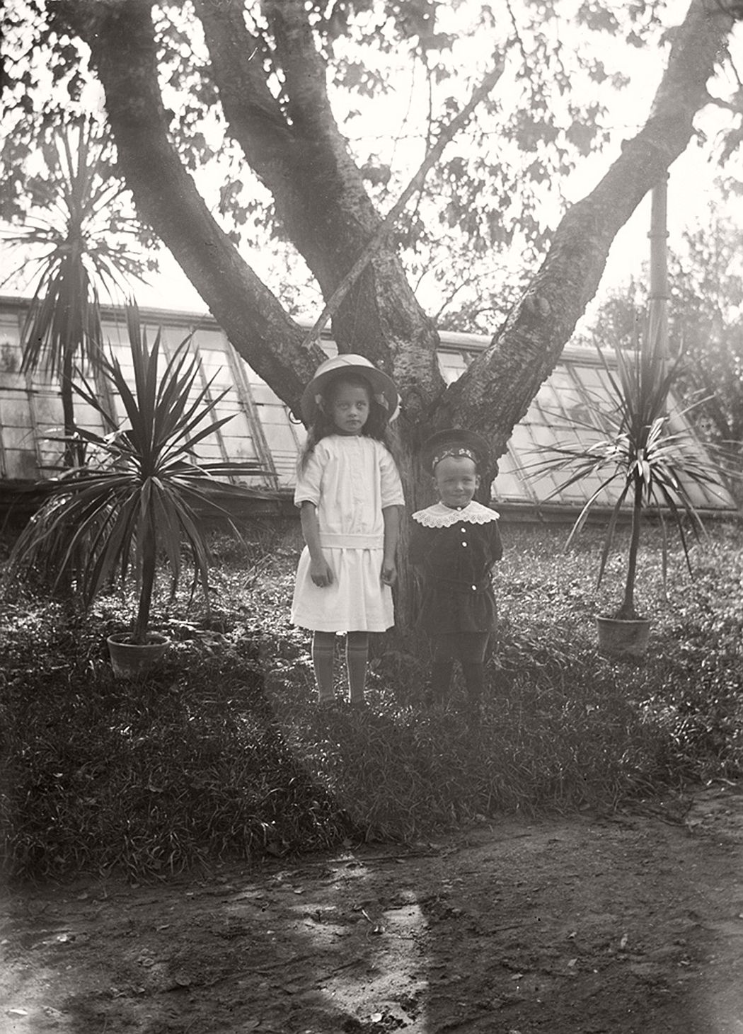 Two children outside the greenhouse.