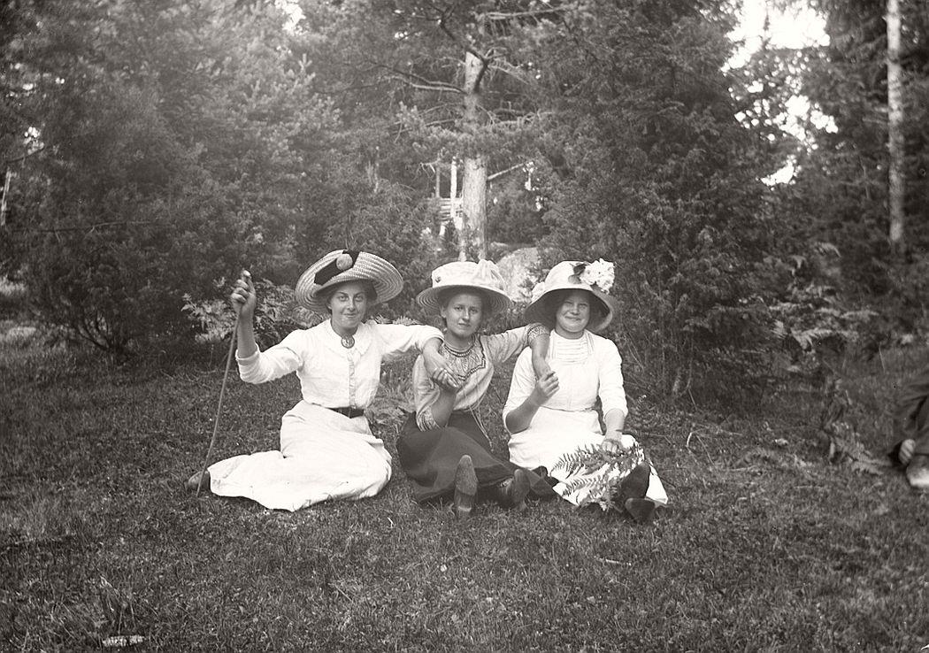 Three happy women sitting on the grass.