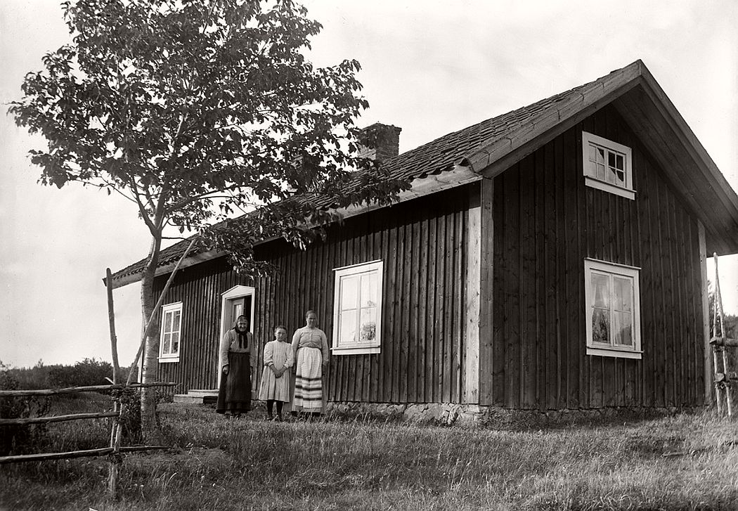 Two women and a girl in front their cottage in Sjöstugan, 1912.