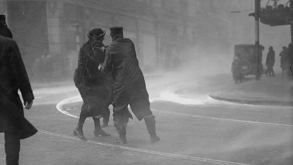 Circa February 1920. Police officer helps woman through blinding snow during a blizzard in Boston.