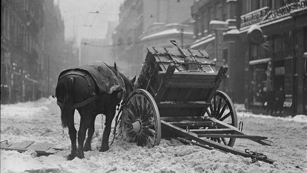 Circa February 1920. Blizzard wreaks havoc on a working horse near South Station, breaking shaft and dumping his load of snow.