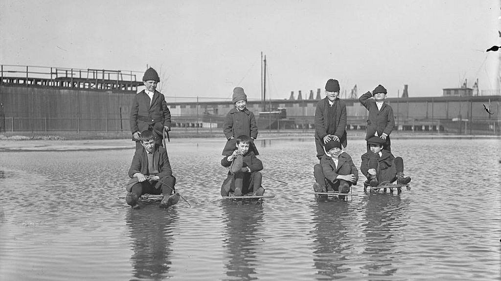 Circa 1921. Kids on sleds plough through water to enjoy ice hidden below.