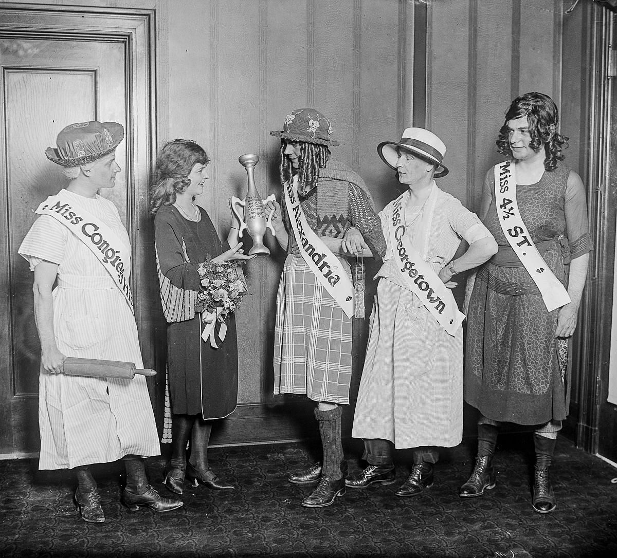 "Sept. 21, 1921 - Gorman presents the wooden loving-cup to ""Miss"" Alexandria Sylvan Oppenheimer, winner of the Advertising Club's ""beauty"" contest. She is flanked by ""Miss Congress Heights"" Allan De Ford, ""Miss"" Georgetown Sidney Selinger and ""Miss Four-and-a-Half Street"" Paul Heller."