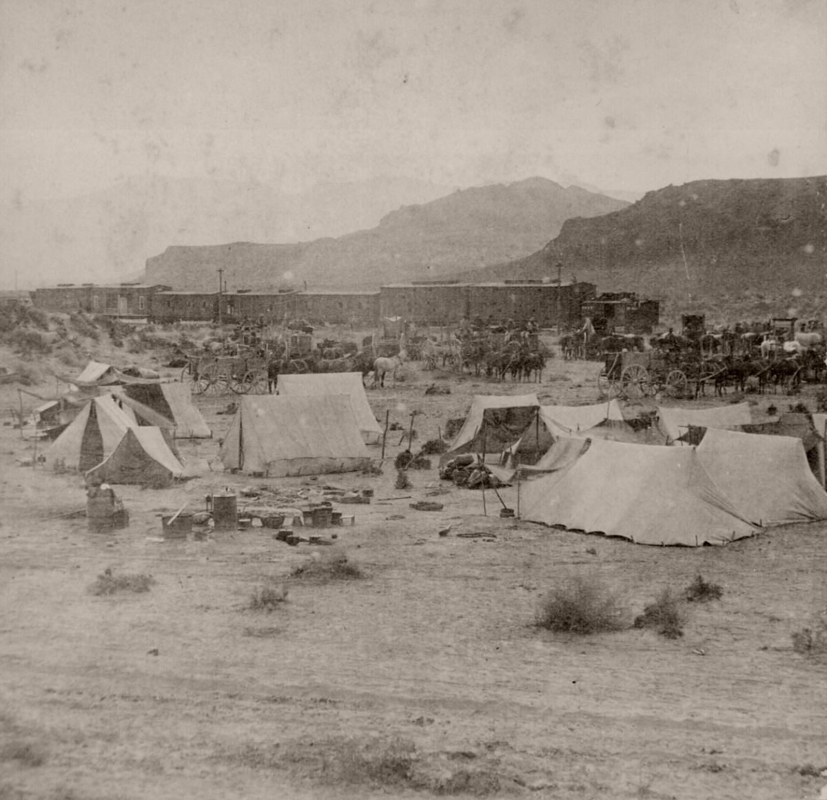 End of the Track. Near Humboldt River Canyon, Nevada. Campsite and train of the Central Pacific Railroad at foot of mountains, 1868.