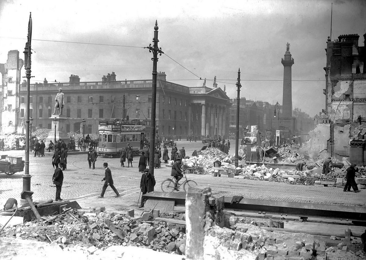 Abbey Street and Sackville Street (O'Connell Street) shelled, rubble remains. The tram passing by was numbered 244. The ads on the tram are for Donnelly's Bacon, Hudson's Super Soap and the Metropolitan Laundry. An ad for Bovil can just be made out on another tram. In the foreground, the bearded man (very nautical vibe) is considering a huge slab on the ground.