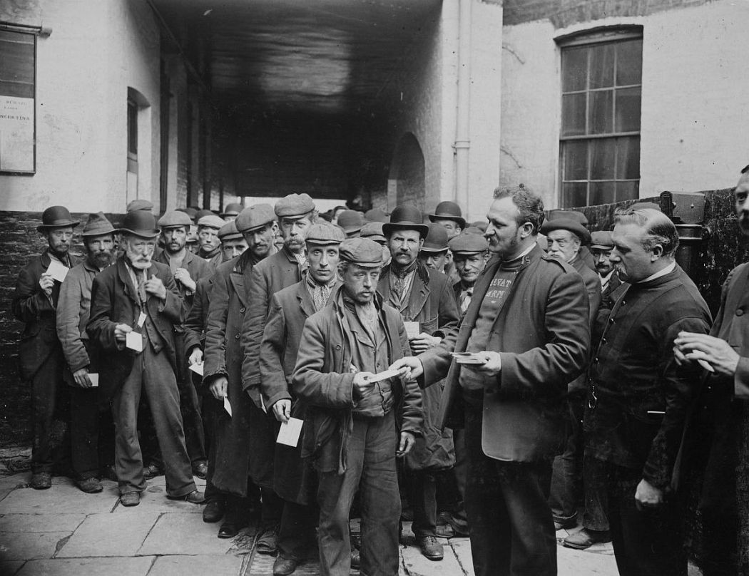 Salvation Army barracks in London during Sunday morning rush – men who had been given tickets during the night queuing for free breakfast, 1902.