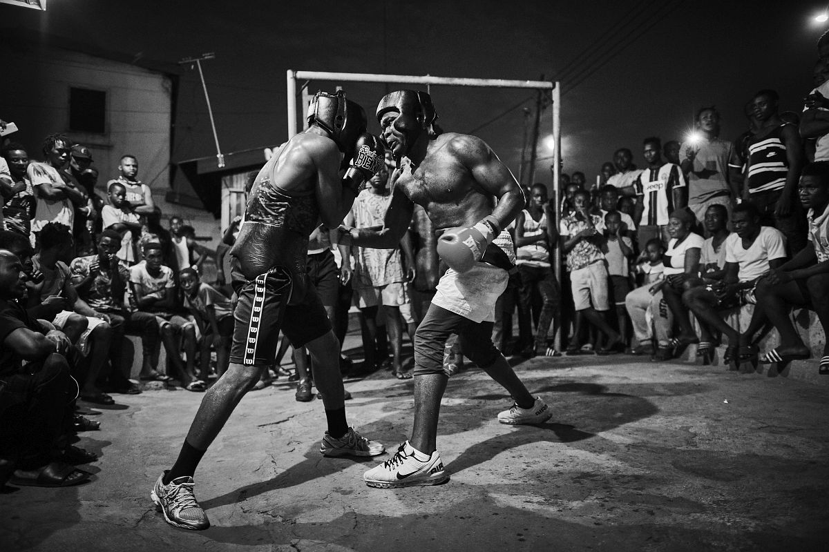 "From Right - Boxer Braimah Kamoko, aka ""Bukom Banku"" sparring with George Ashie aka ""Red Tiger"" at ""Wadada Boxing Gym"" in preparation for Kamoko´s fight with Bastie Samir. Accra, Ghana, October 4th, 2017.<br /> Crowds of cheering fans encircle the two boxers to cheer on their hero ""Bukom Banku"". Many of these fans have run long distances to support the boxers in their training session."