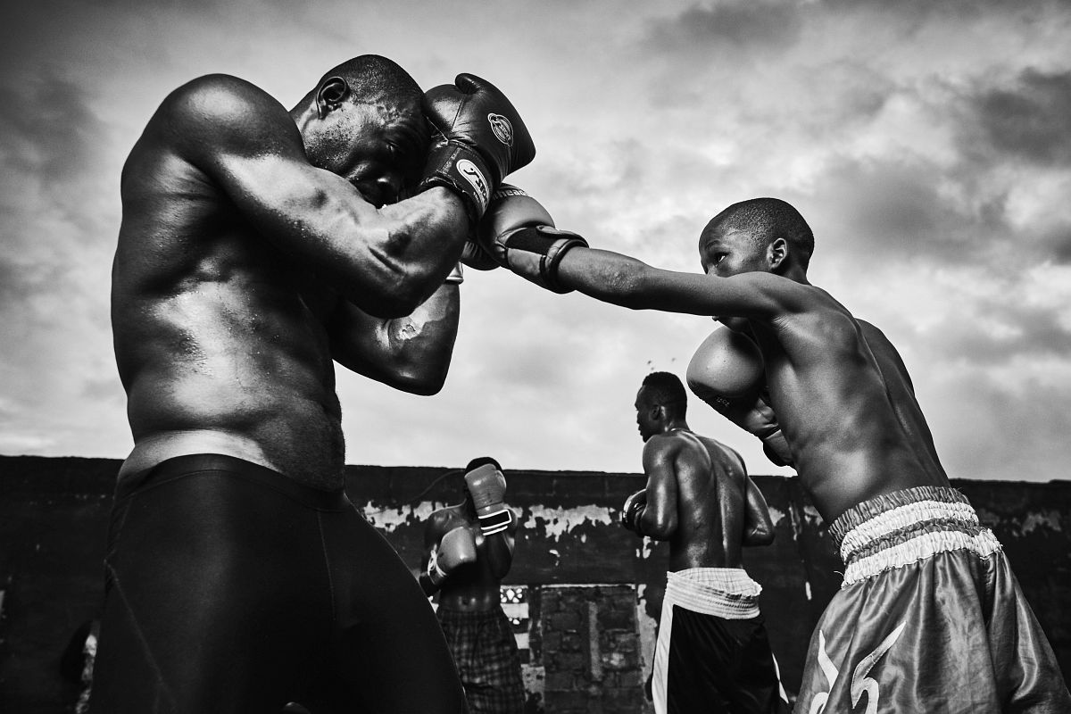 "From left - Boxers Atu Ricketts and Emmanuel Fofo Mawuli sparring during training at ""Charles Quartey Boxing Foundation"", in Accra, Ghana, on September 29th, 2017. Young up and coming boxer Emmanuel Fofo Mawuli lands a punch on the defense of Atu Rickets. ""Fofo"" trains along with the adults and current champions at Charles Quartey Boxing Foundation as he grows up in boxing."
