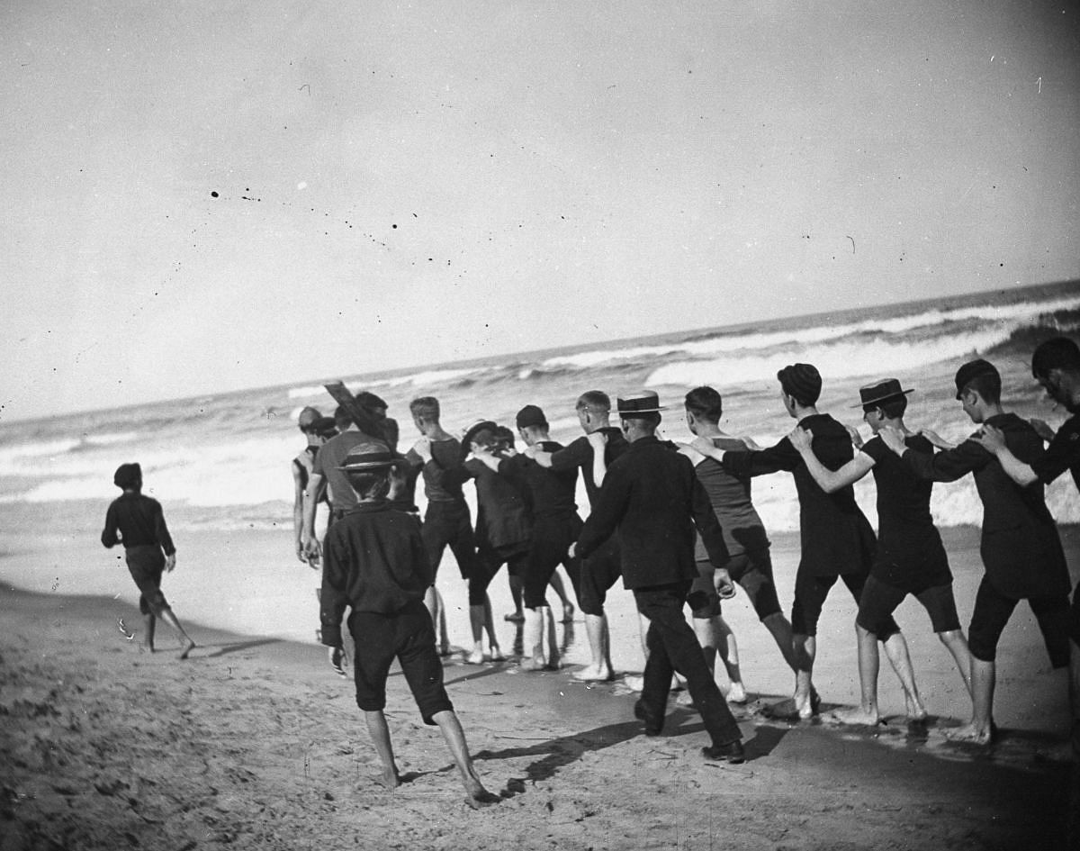 Aug. 23, 1886 - A group of young male bathers walk single file along the beach.
