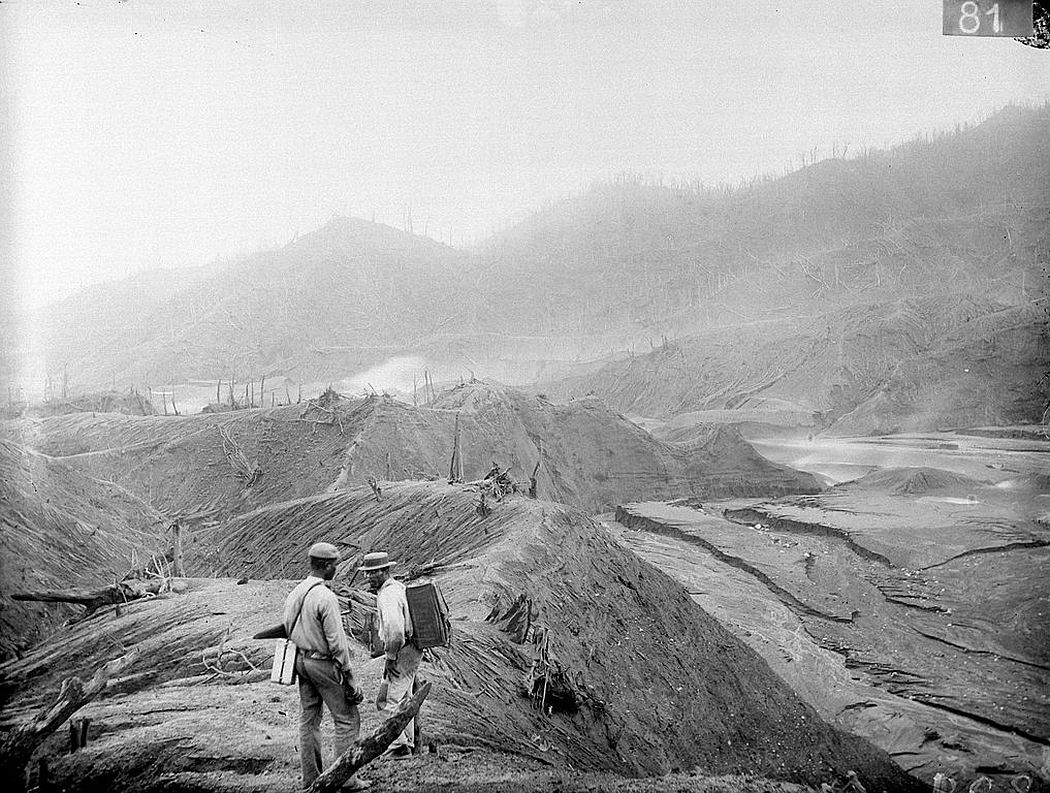 Two men, carrying boxes which contain Tempest Anderson's photographic equipment, can be seen in the foreground, Rabaka, Saint Vincent (1902)