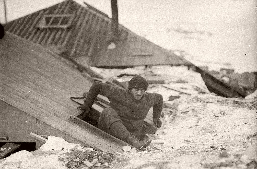 Mertz leaving the hut by the trapdoor on the verandah roof, circa 1912