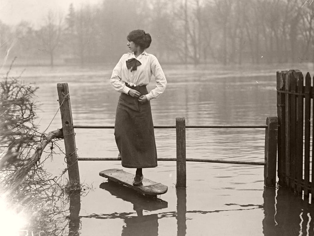 A woman crossing a stile after the flooding in the Thames Valley, December 1915.