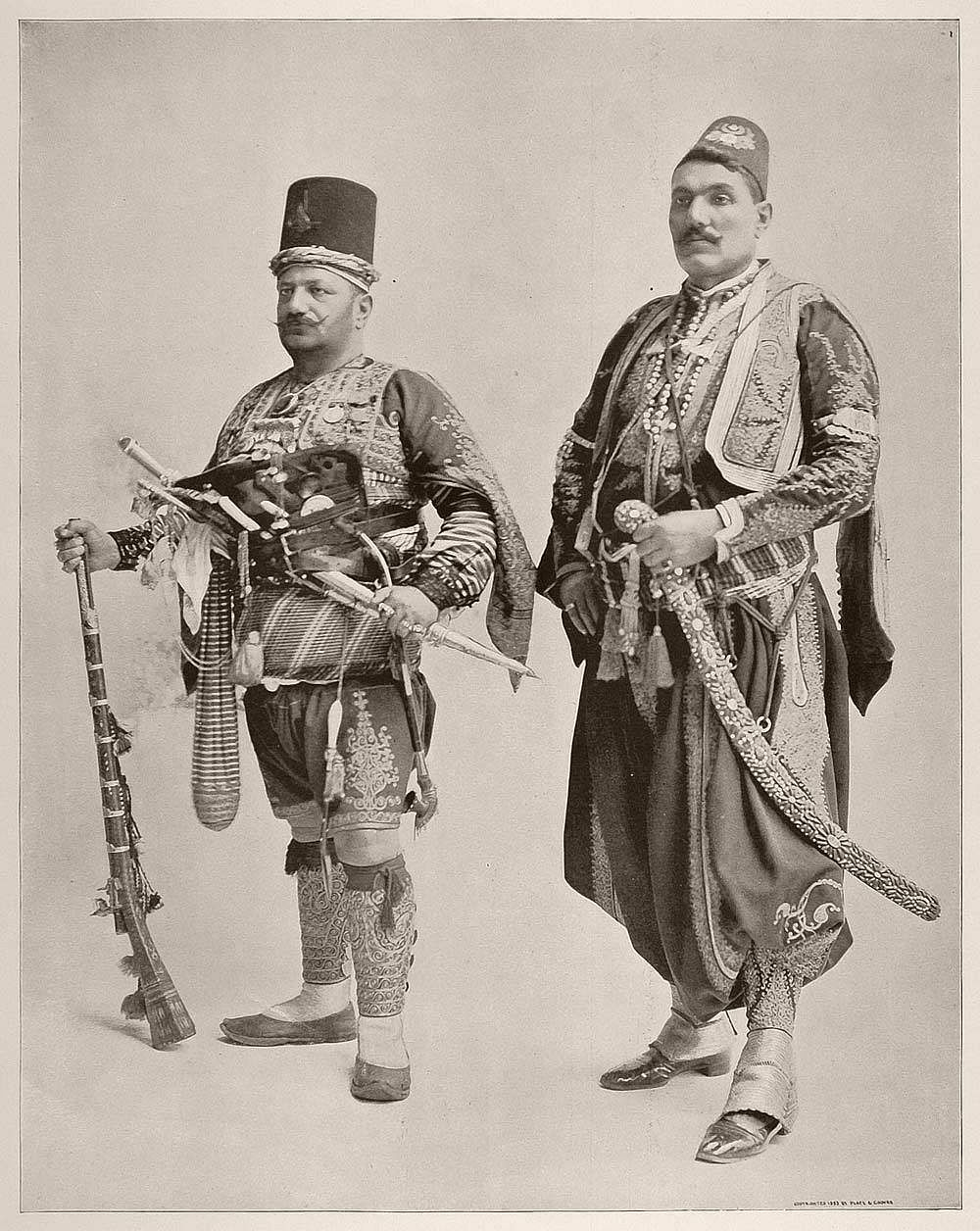 Nichan, an Armenian man in the uniform of the Janizaries, a Turkish military band of soldiers. The figure on the left is a Greek man.