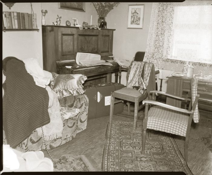 Interior with piano, suitcase and chairs. Details unknown, early 1950s.