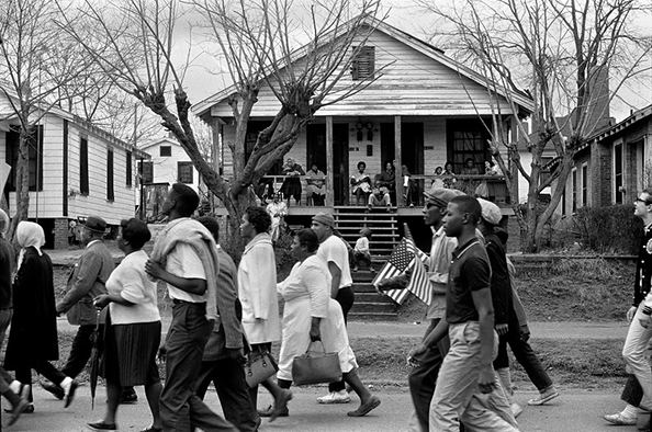 Stephen Somerstein Selma to Montgomery civil rights marchers passing by house with people, African-American and white man holding small American flag in Montgomery, Alabama on March 25, 1965