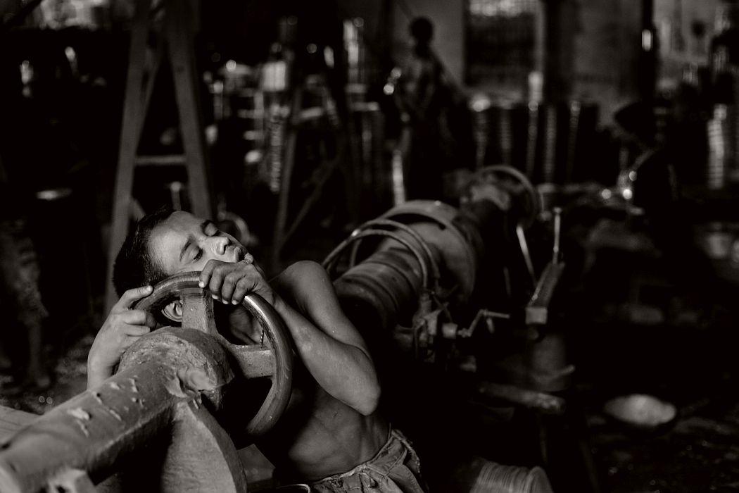 09-  Shakil falls asleep on his tools after hard work at aluminum factory. Aluminum Factory in Chittagong, Bangladesh .