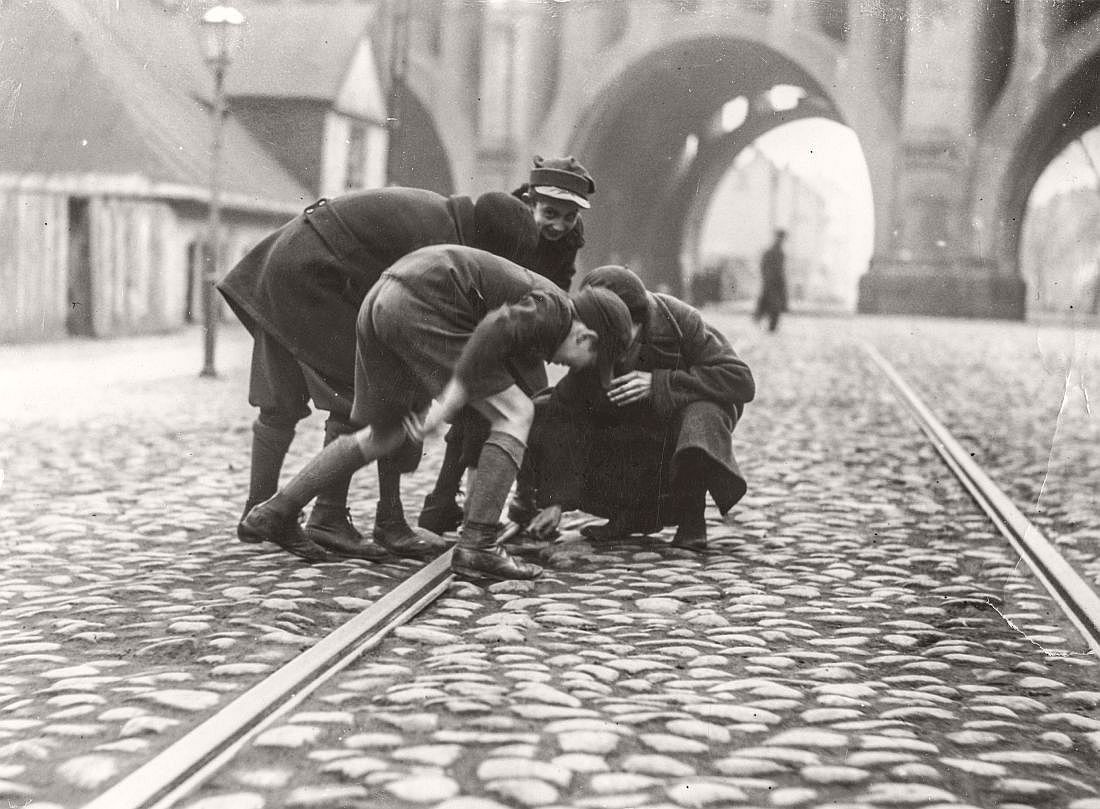 A group of boys during dubbing firecrackers at trams on the tracks, Warsaw, 1933