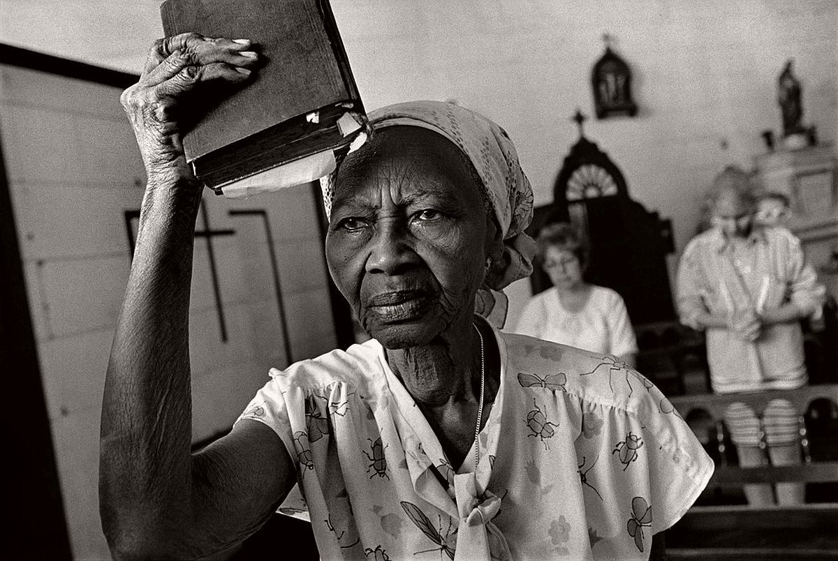 "CUBA. Havana. 1997. Church of Cristo de Buen Viaje. A woman listening to a sermon raises her Bible as a flag, before going to visit homes to take in ""the Lord's words"". Up to the late 1990s, proselytism was strictly prohibited in Cuba."