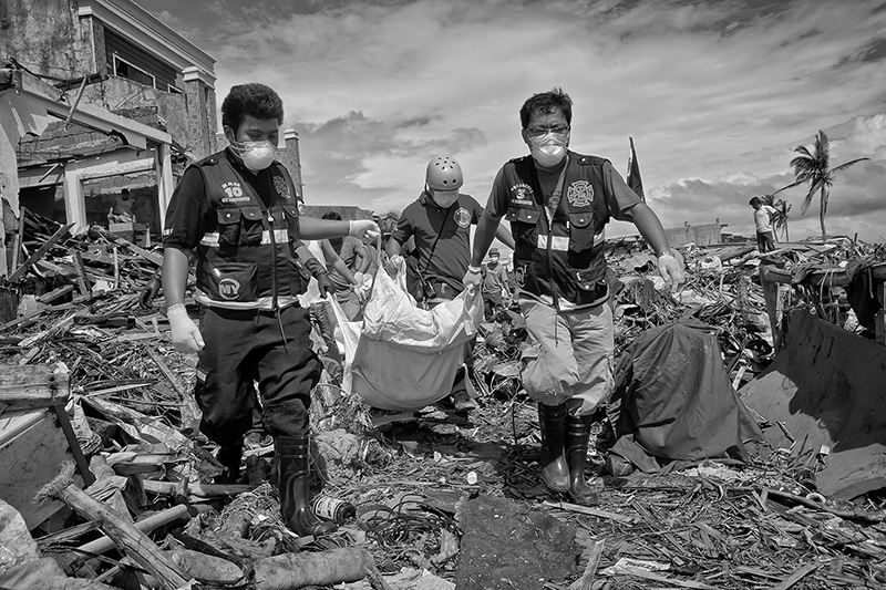 The amount of casualties left behind the typhoon Haiyan will never be known.  When the hope for recovering survivors was almost none, many rescue teams arriving from different nations realized that they had to concentrate into recovering all the corpses they could find as soon as possible in order to prevent the spread of epidemics. Many of the teams such as the Korean Rescue Team proved to be extremely experienced and carried all the tools required for the search, which meant excavating, cutting into the debris with chainsaws, a very big amount of body bags and a fast and coherent interaction which whatever obstacles they found. The majority of the rescue teams possessed rescue dogs, which were both trained for finding survivors as the main priority and corpses as second. When the search for corpses was heavily implemented, the rescue units followed the dog until it stopped on a pile of debris which hid some human remains; if the operation seemed too complicated due to the amount of debris covering the body, the team would automatically switch onto the search of another body.   The chances of finding abundant human remains were very high at the very populated slum areas, in which the poor constructions had been devastated by the wind and the uprising of the waters. Most of the bodies were brought to huge mass graves in the outskirts of Tacloban to be buried as soon as the circumstances allowed. There was even an attempt on the part of the forensic team –whenever it was possible- to gather evidence to identify the human remains, and the forensic team worked endlessly both day and night for that purpose. Many other times it was an impossible effort.