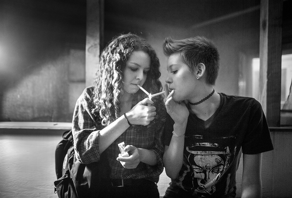 Two girls share a lighter during a smoke break while Minneapolis band Royal Brats perform at a Iowa City home on Friday, Feb 19, 2016. (The Daily Iowan/ Jordan Gale)