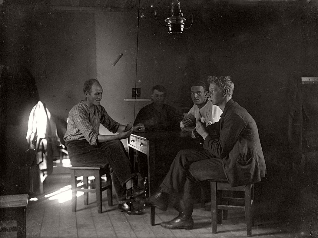 Four men playing cards, ca. 1920s.
